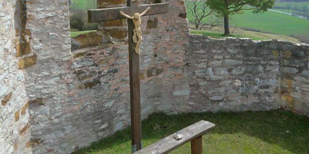Ein Kreuz auf einem Berg, davor eine Bank,© ELKB / Lutz Neuschwander