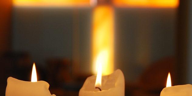 Kerzen vor einem leuchtenden Kreuz,© ELKB / Christina Mayer