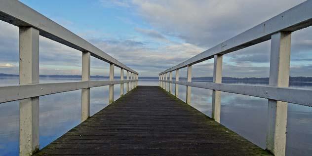 Das Bild zeigt einen Steg, der an einem See ins Weite führt